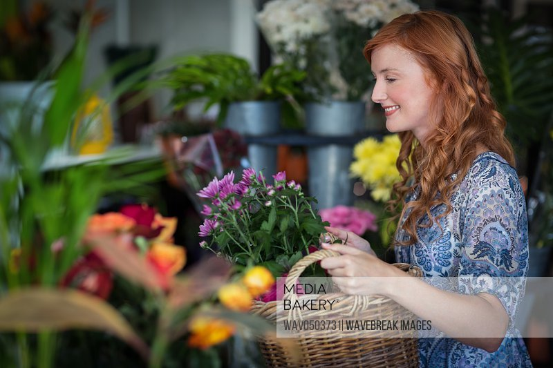 Smiling female florist holding basket of flowers in the shop