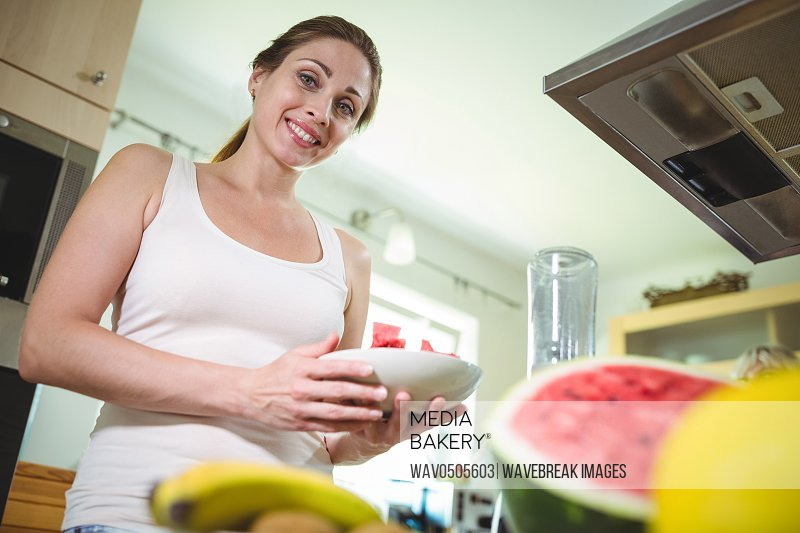 Smiling woman holding a plate of watermelon in kitchen