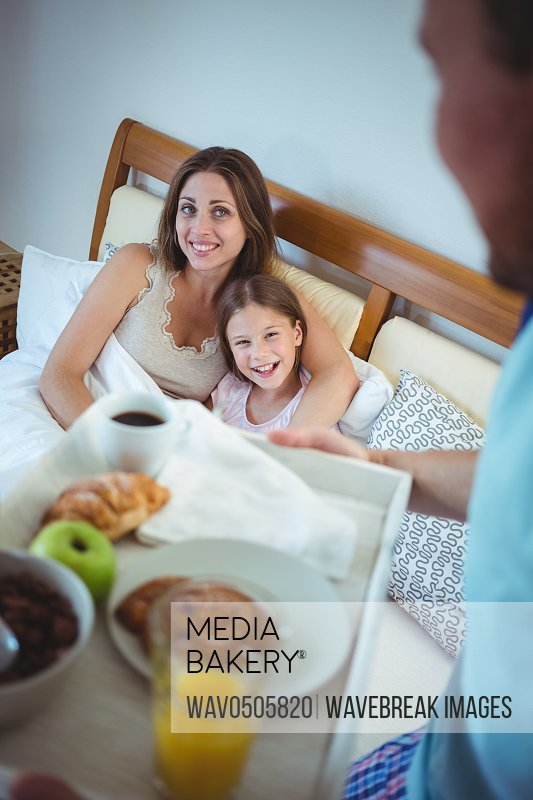 Father carrying tray with breakfast for mother and daughter in bedroom