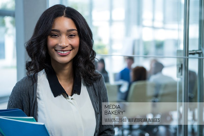 Portrait of beautiful businesswoman holding files in office