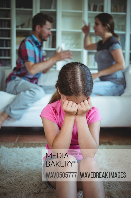 Sad girl crying while parents arguing in living room at home