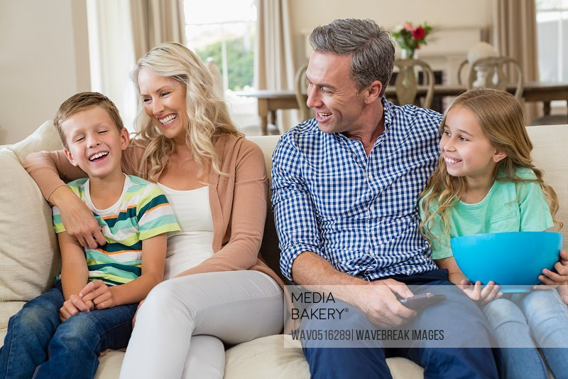 Parents and kids having fun while watching tv in living room