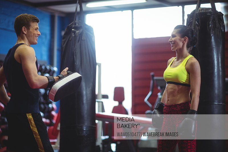 Boxer and trainer interacting with each other in fitness studio