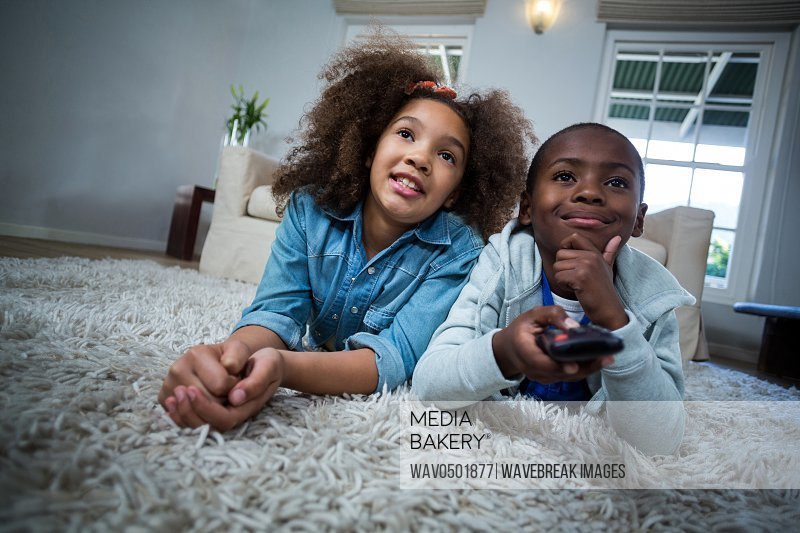 Children holding remote while lying on the floor at home