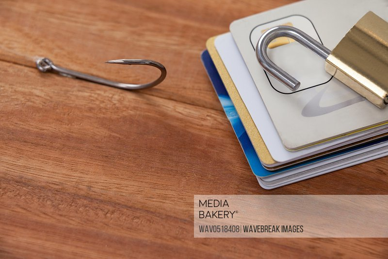 Bunch of credit cards fishing hook and lock on wooden background