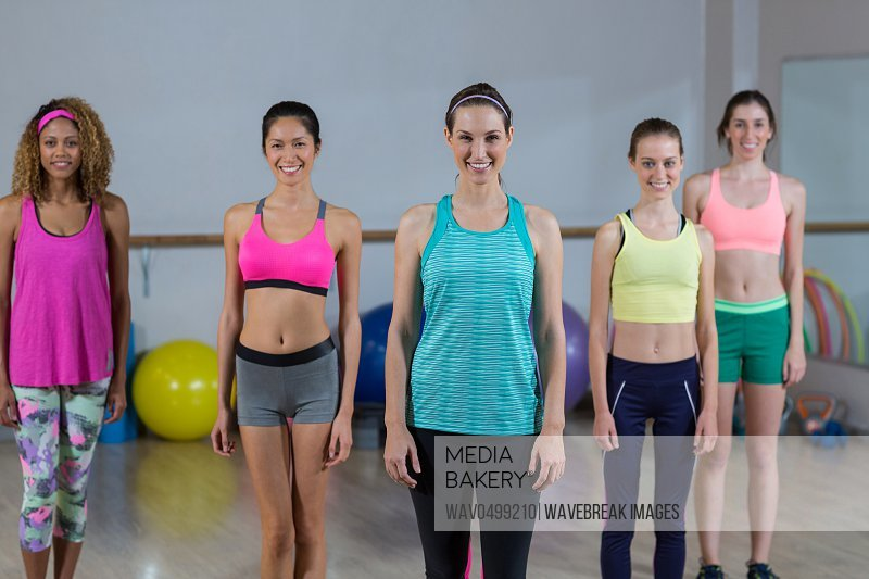 Portrait of group of fitness team standing in fitness studio