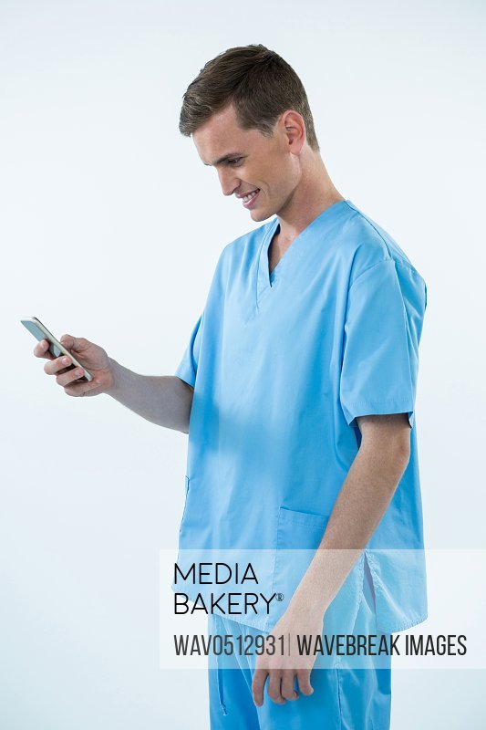 Smiling male nurse using mobile phone against white background