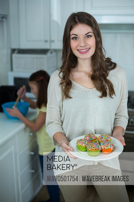 Woman holding a plate of cupcakes in kitchen