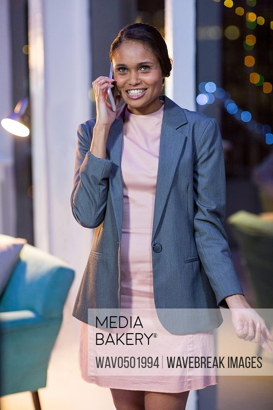 Businesswoman talking on mobile phone in office at night