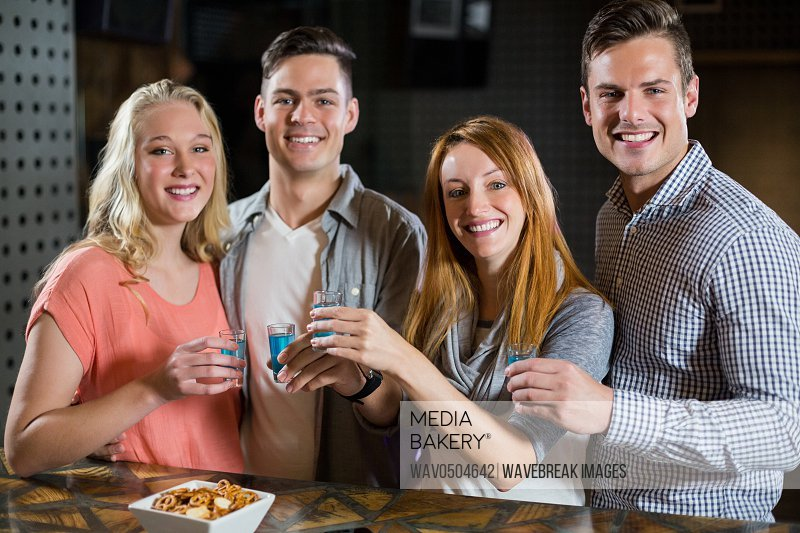 Portrait of smiling friends standing at bar counter and having tequila shots in bar