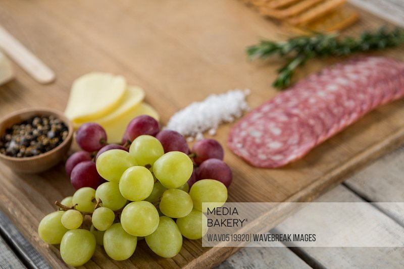 Grapes and ham with various ingredients on chopping board