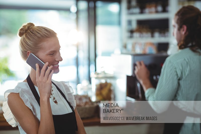 Smiling waitress talking on mobile phone in cafe