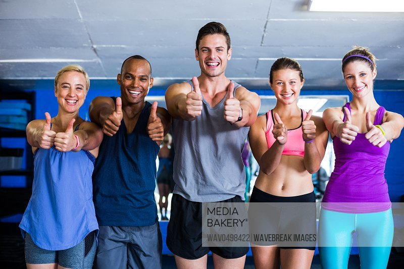 Portrait of smiling friends showing thumbs up while standing in gym