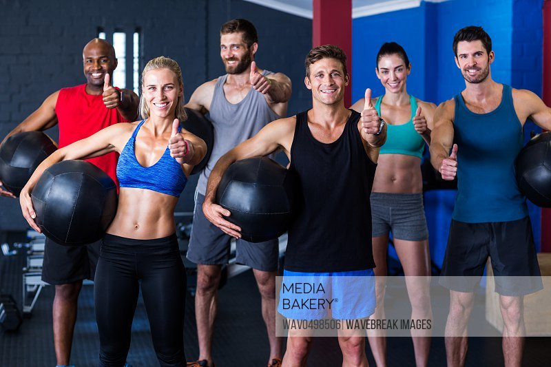 Portrait of happy friends showing thumbs up while standing in gym