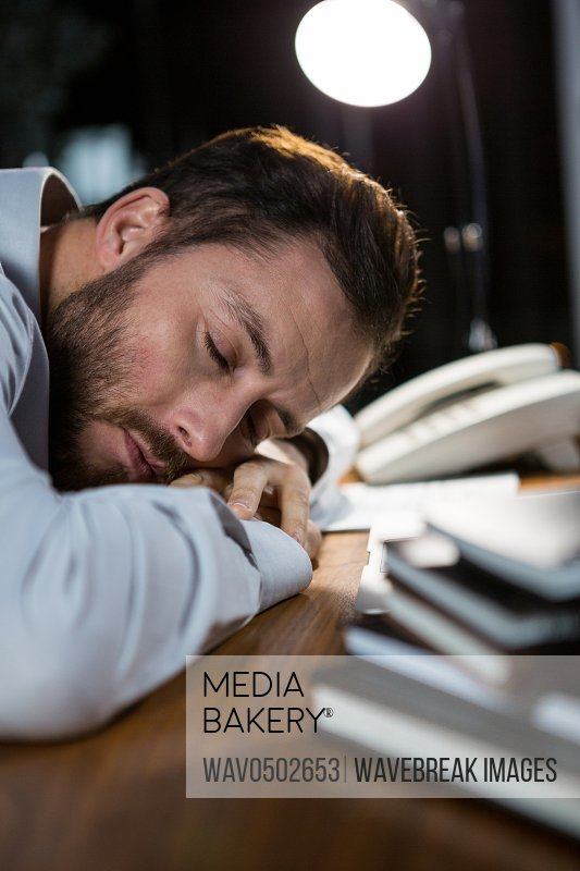 Close-up of tired businessman sleeping on the desk in office at night