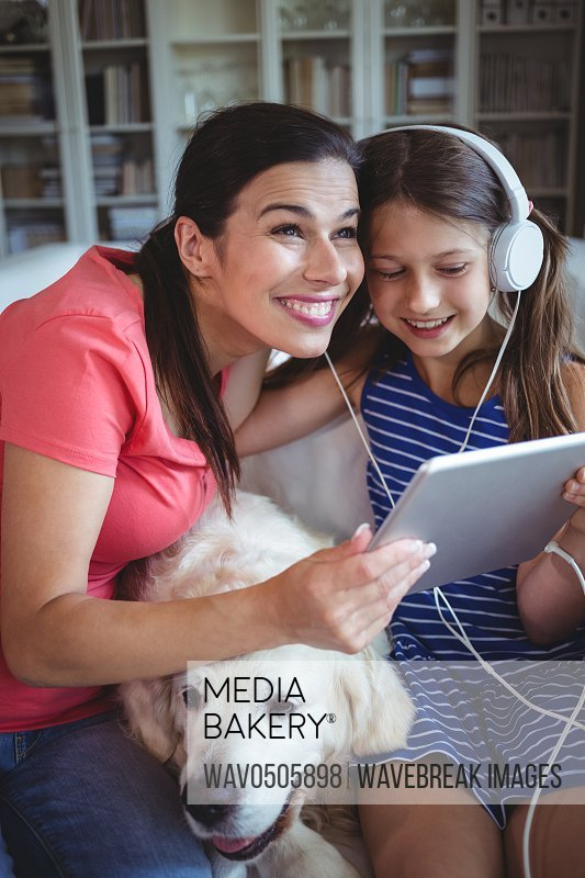 Happy mother and daughter sitting with pet dog and listening to music on headphones at home