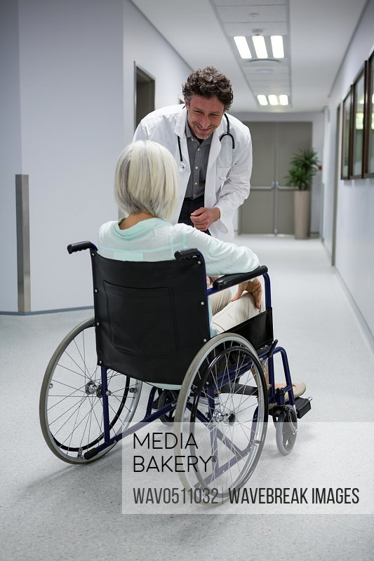 Doctor interacting with patient sitting on wheelchair in corridor at hospital