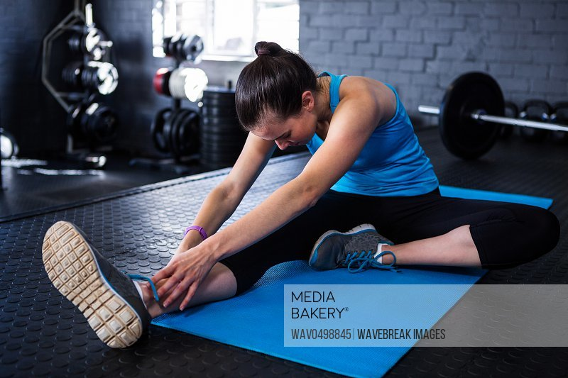 Young athlete stretching while sitting in gym