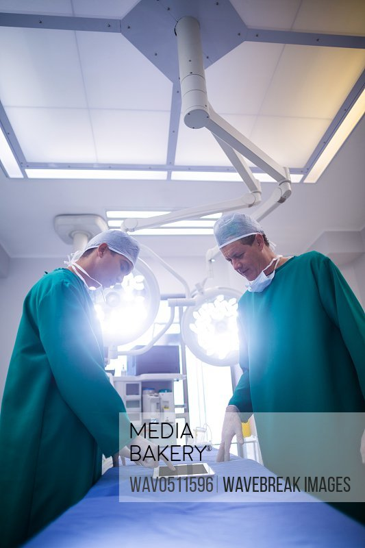 Surgeons discussing over digital tablet in operation room at hospital