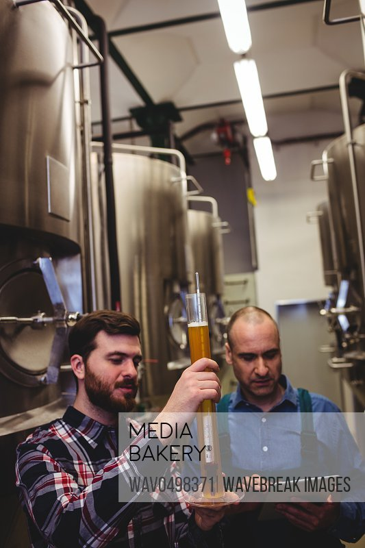 Worker and owner inspecting beer amidst machinery at brewery