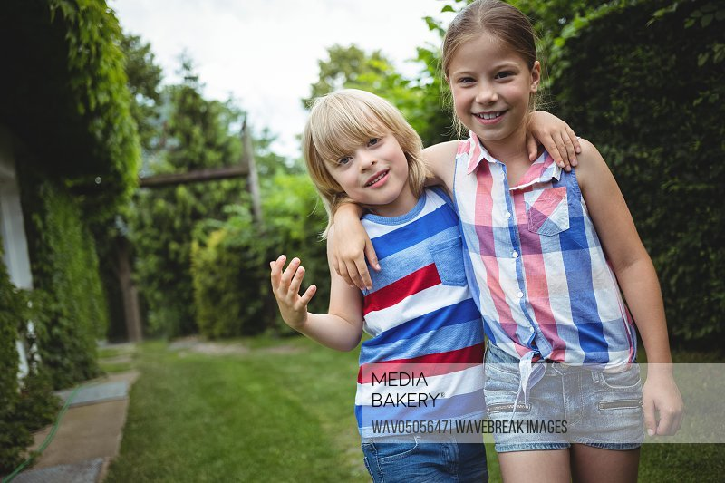 Portrait of kids standing with arms crossed in park on a sunny day