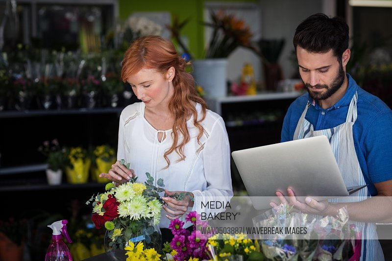 Woman preparing flower bouquet while man using laptop in the flower shop