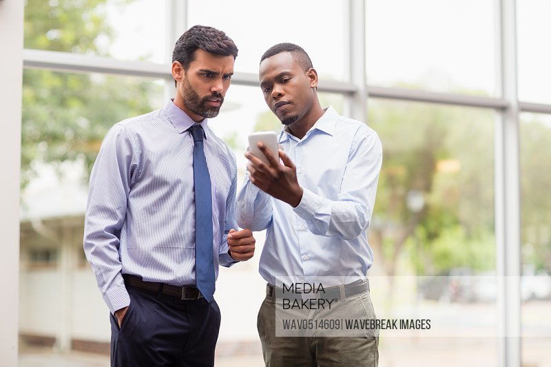 Business executives discussing over mobile phone