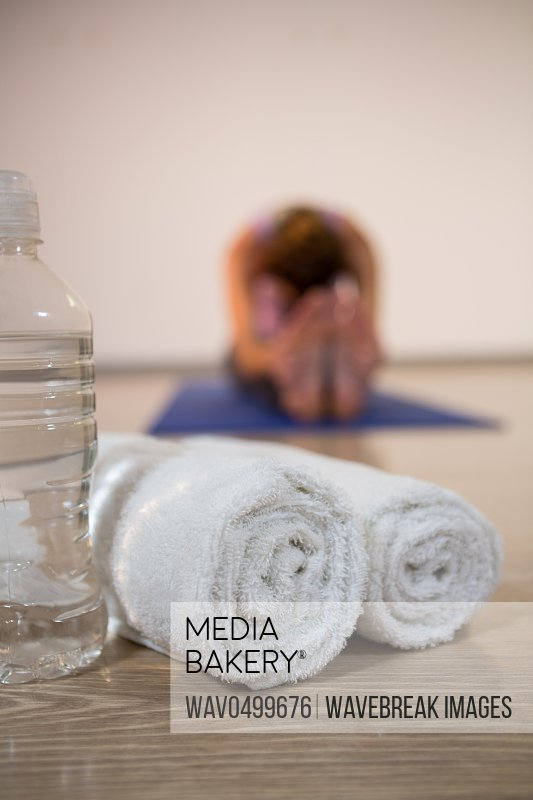 Close -up of rolled towels and water bottle in fitness studio