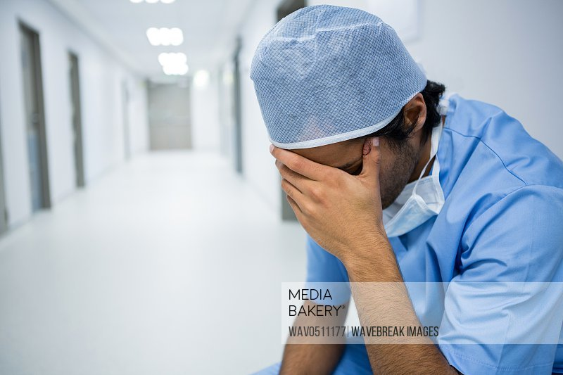 Tensed surgeon sitting with hand on forehead in corridor of hospital