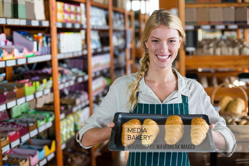 Portrait of smiling female staff holding tray of croissants in supermarket