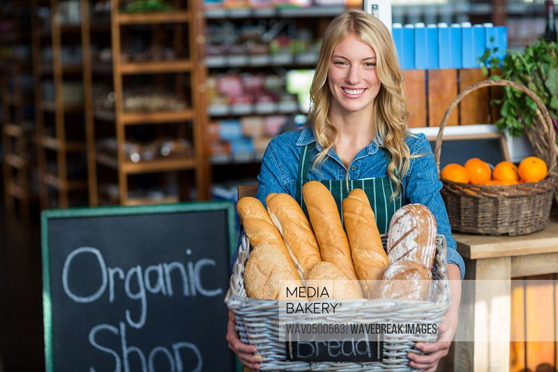 Smiling woman holding a basket of baguettes in organic shop of supermarket
