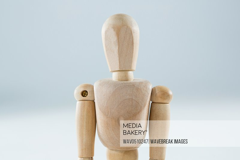 Wooden figurine standing against white background
