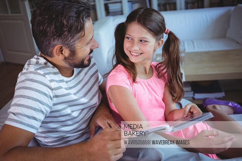Father and daughter looking photo album on bed at home