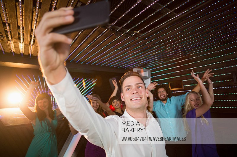 Man taking a selfie from mobile phone while friends dancing at bar