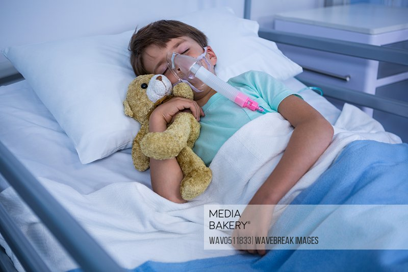 Patient with oxygen mask relaxing on bed in ward at hospital