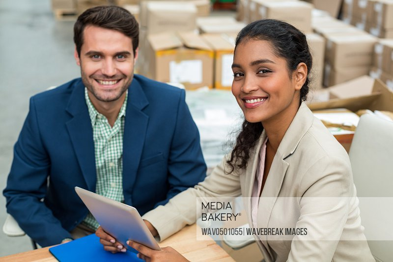 Portrait of two warehouse managers using digital tablet in warehouse office