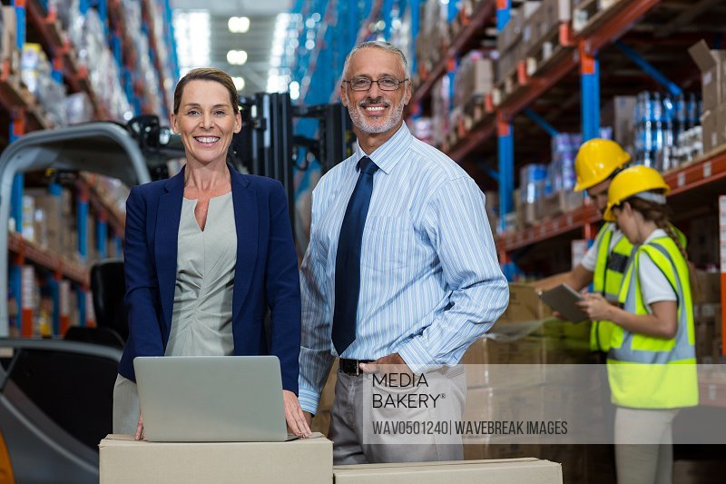 Portrait of warehouse manager and client standing with laptop in warehouse