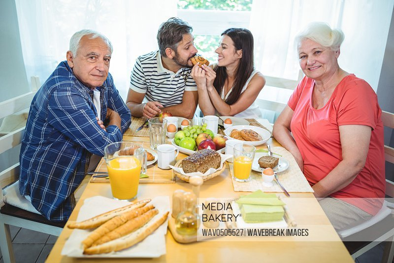 Happy couple having breakfast with their parents at home