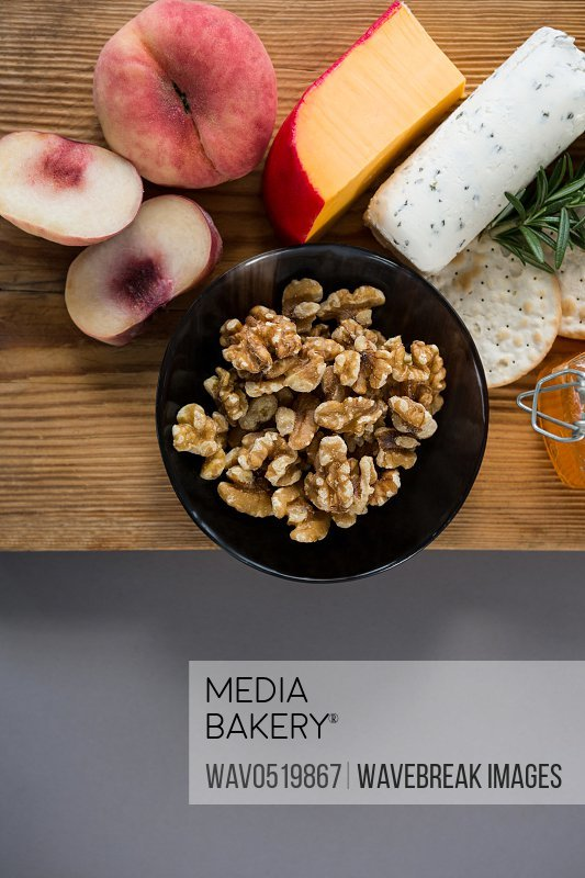 Variety of cheese with peach honey rosemary walnuts and crackers