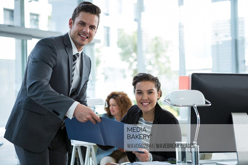 Portrait of businesspeople discussing over document in office