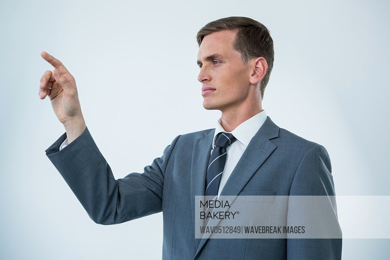 Businessman touching an invisible screen against white background