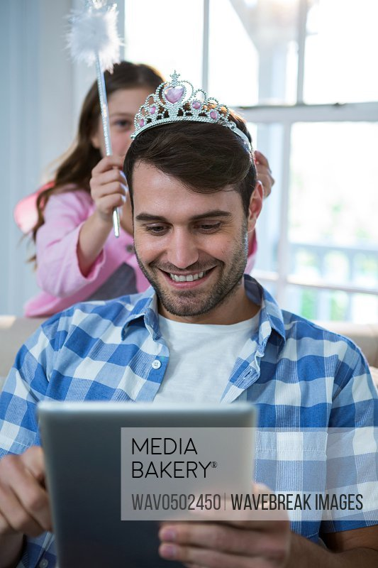 Girl dressed up in a fairy costume placing tiara on fathers head at home