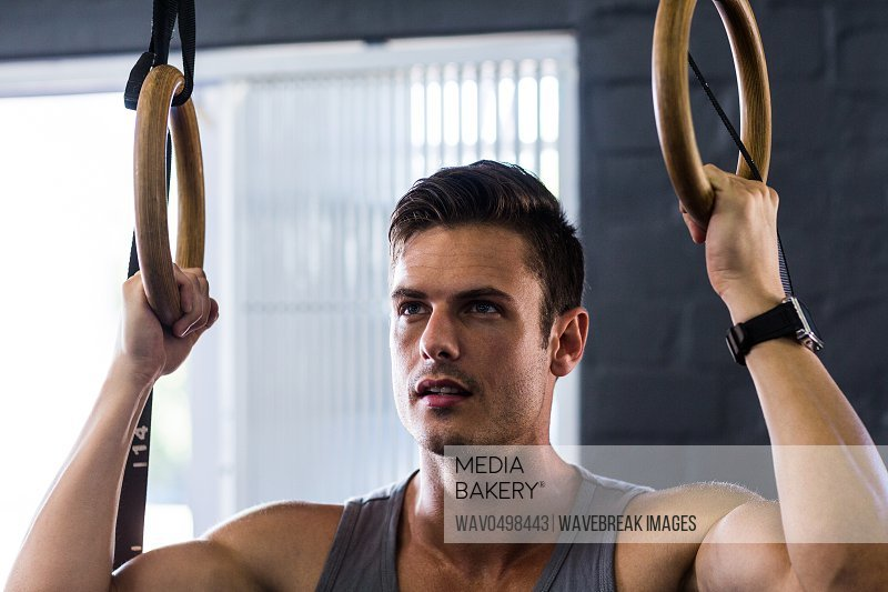 Close-up of young man using gymnastic rings while exercising in gym