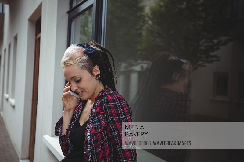 Woman talking on mobile phone outside the building