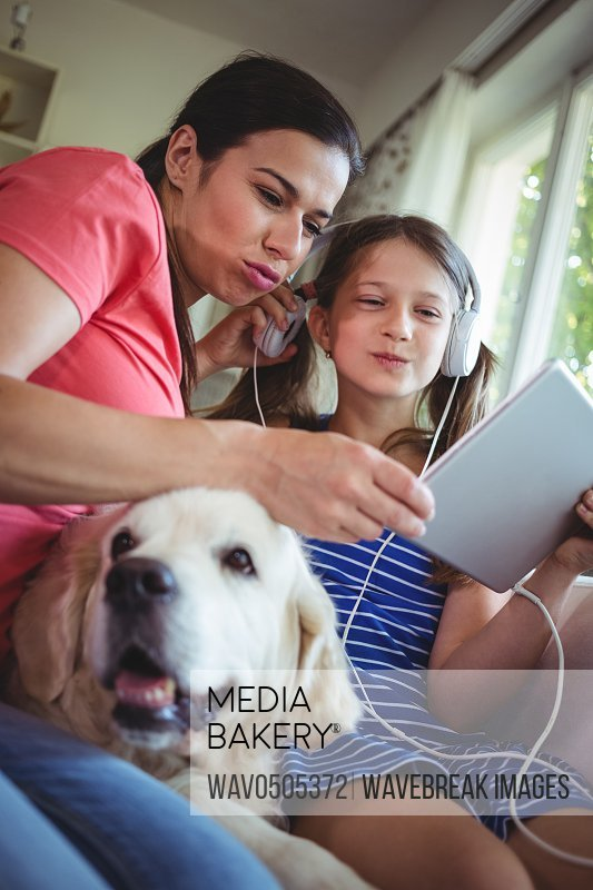 Mother and daughter sitting with pet dog and using digital at home