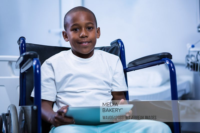 Portrait of boy sitting on wheelchair with digital tablet in ward at hospital