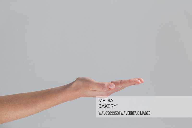 Close-up of cupped hand of a woman against grey background