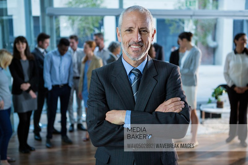 Portrait of happy businessman standing with arms crossed in office