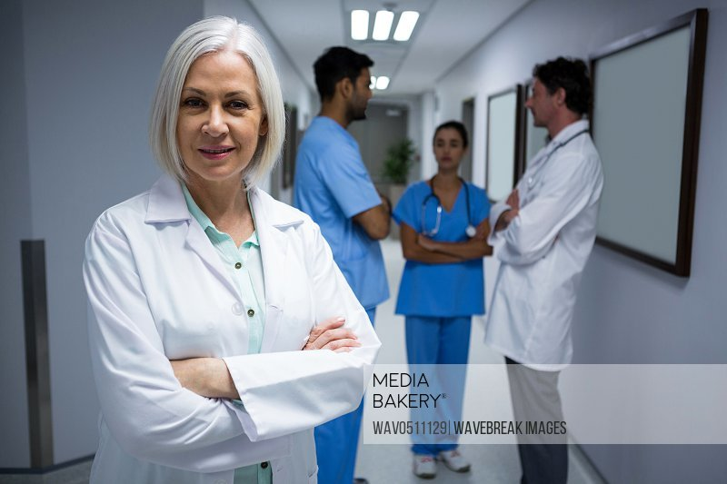 Portrait of doctor standing with arms crossed in corridor while surgeons discussing in background at hospital
