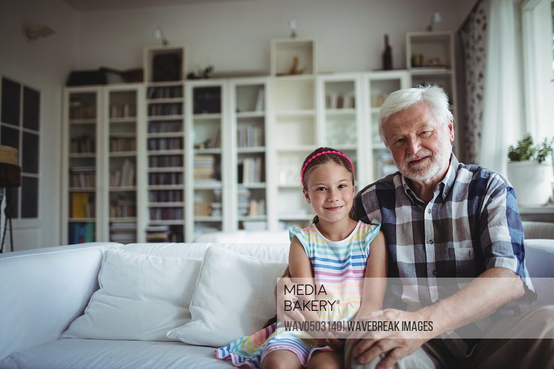 Portrait of senior man sitting with his granddaughter at home